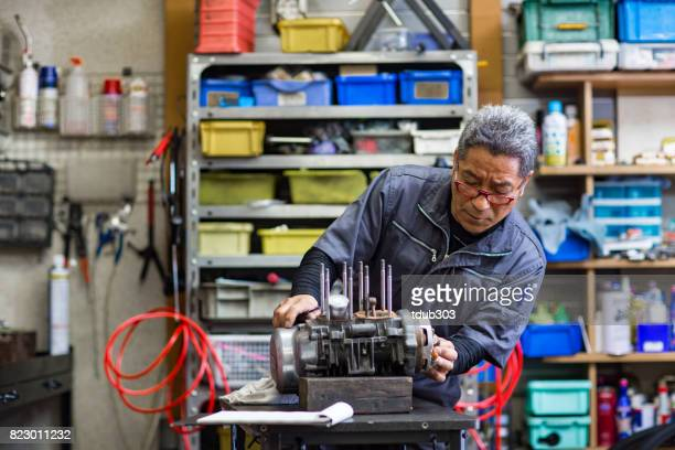 senior mechanic repairing a motorcycle engine in his small business garage. - working seniors stock pictures, royalty-free photos & images