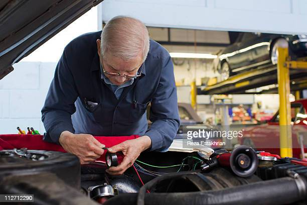 Senior mechanic repairs electrical wires in auto