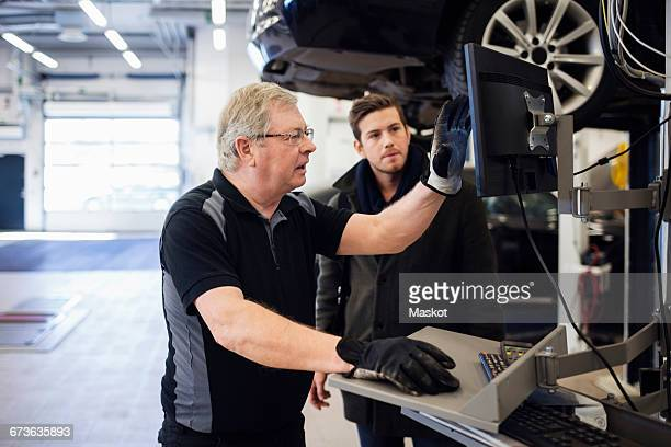 Senior mechanic showing computer monitor while discussing with customer at repair shop