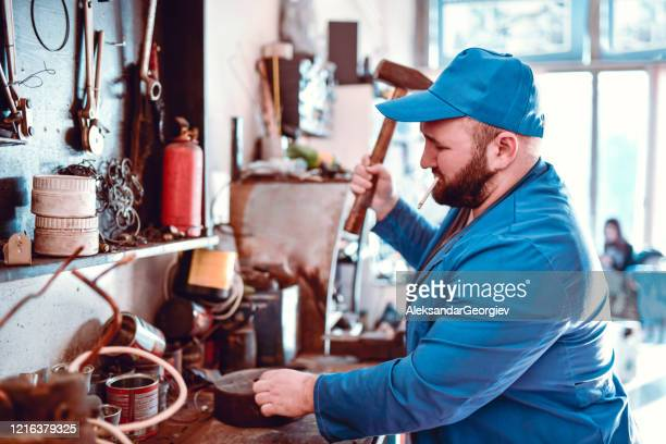 senior mechanic smoking in car workshop and fixing part with a hammer - strike industrial action stock pictures, royalty-free photos & images