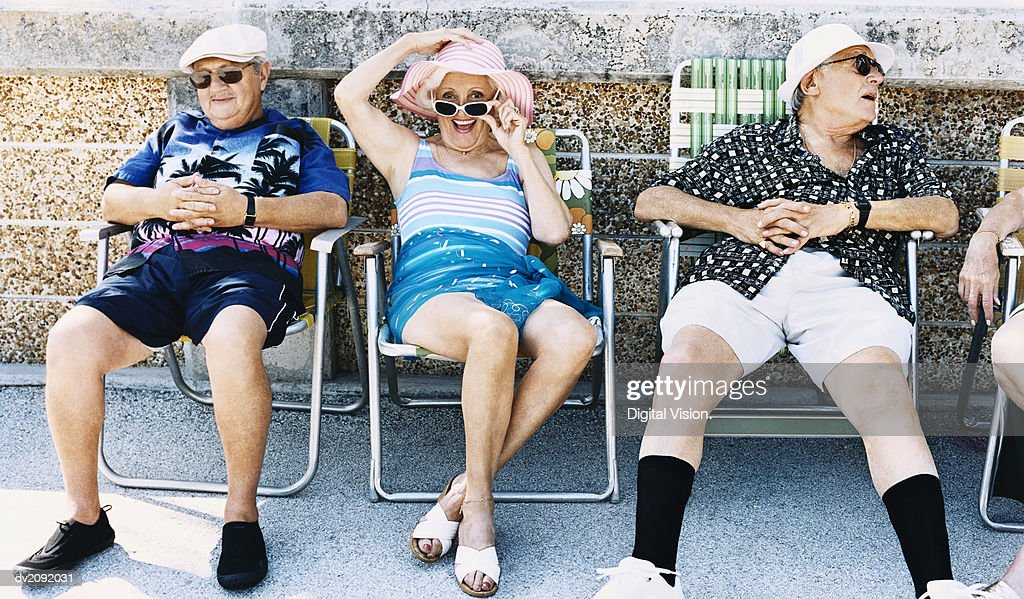 Senior Men and a Woman Sit on Deckchairs on the Pavement Sunbathing : Stock Photo