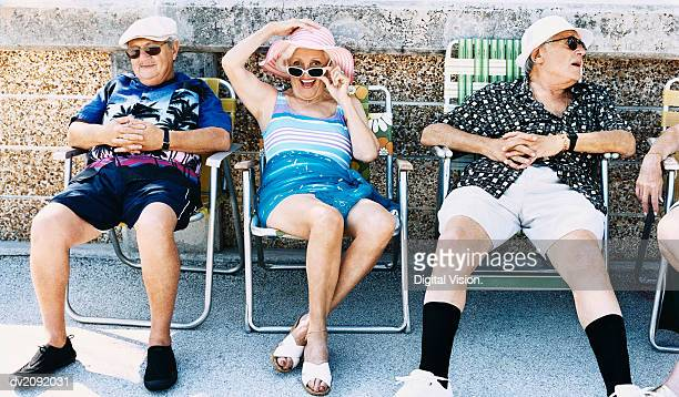 Senior Men and a Woman Sit on Deckchairs on the Pavement Sunbathing