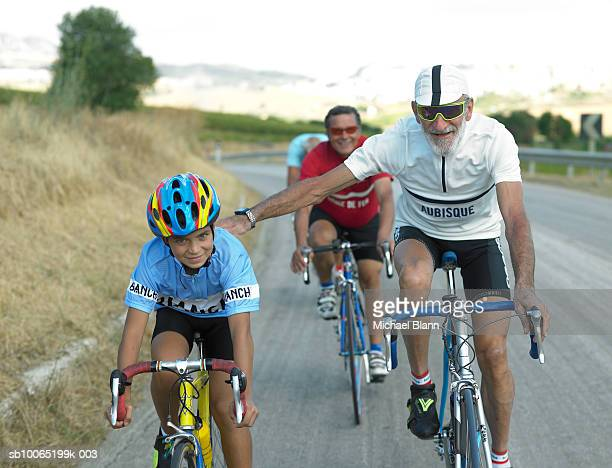Senior men and boy (10-11) cycling along country road