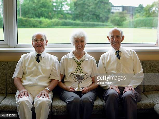 Senior Men and Senior Woman Sitting in a Lawn Bowling, Woman Holding a Trophy