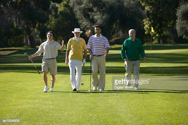 senior men and their mature sons walk side by side on a putting green, laughing - four people stock pictures, royalty-free photos & images