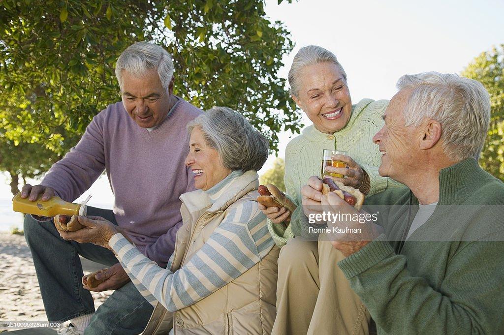 Senior men and women eating at beach, smiling : Foto stock