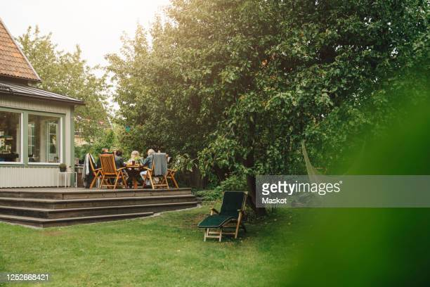 senior men and women enjoying dinner while sitting dining table during garden party - front or back yard stock pictures, royalty-free photos & images