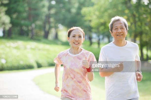 ジョギングをするシニアの男女 - 恩給生活者 ストックフォトと画像