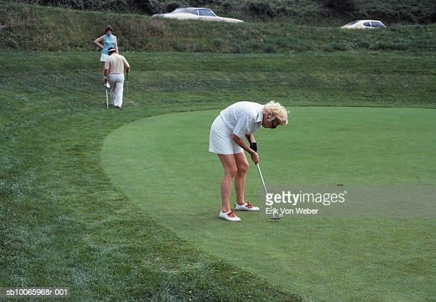 senior men and women playing golf - putten stockfoto's en -beelden