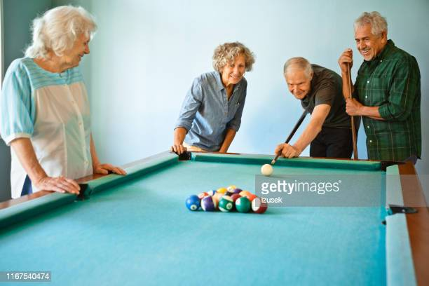 senior men and women playing pool ball at home - old men playing pool stock pictures, royalty-free photos & images