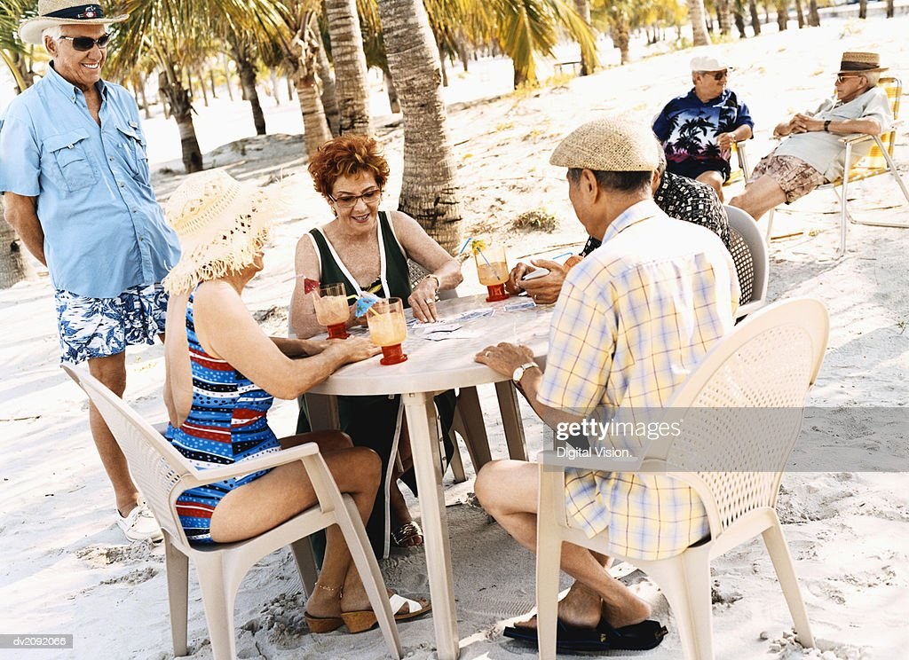 Senior Men and Women Sit at a Table on the Beach Playing a Game of Cards : Stock Photo