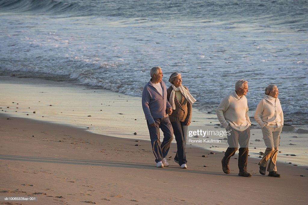 Senior men and women walking at beach : Foto stock