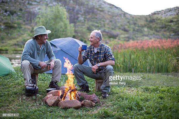 senior men camping outdoors - campfire stock pictures, royalty-free photos & images
