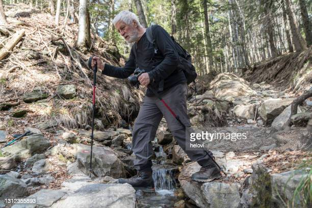 senior men crossing mountain spring - silver boot stock pictures, royalty-free photos & images
