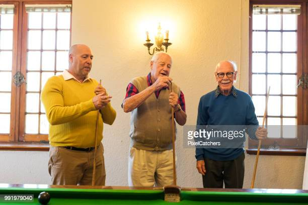 senior men each holding a cue stick - old men playing pool stock pictures, royalty-free photos & images