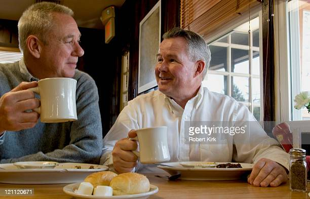 senior men eating and drinking coffee - diner stock pictures, royalty-free photos & images