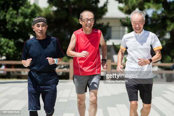 senior men enjoying jogging with friends - japanese old man stock pictures, royalty-free photos & images