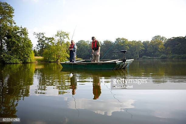 Senior men fishing together on lake