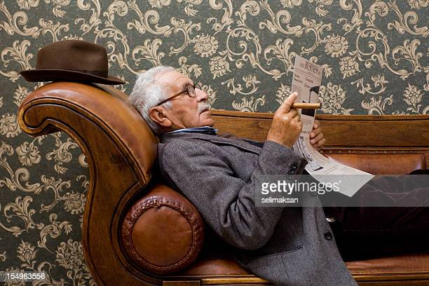 Senior men lying down on sofa and reading newspaper