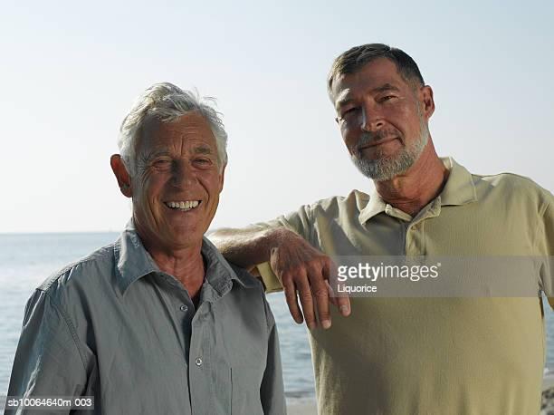 Senior men on beach, smiling, portrait