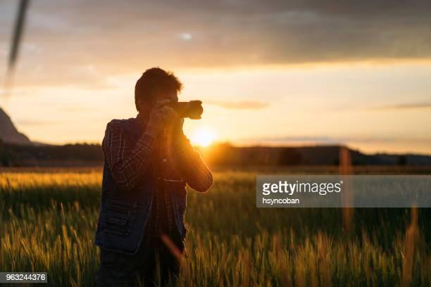 homens altos, fotografando o pôr do sol - fotógrafo - fotografias e filmes do acervo