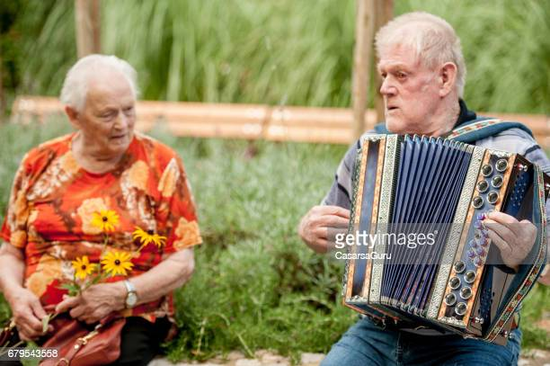 senior men playing accordation in the garden of the retirement community - accordionist stock pictures, royalty-free photos & images
