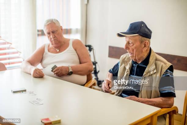 senior mannen speelkaart voor ontspanning in het verpleeghuis - alleen seniore mannen stockfoto's en -beelden
