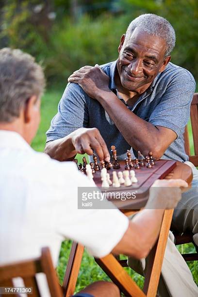 Senior men playing chess in park