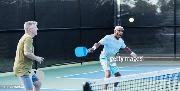 senior men playing paddleball, hitting ball - racket sport stock pictures, royalty-free photos & images