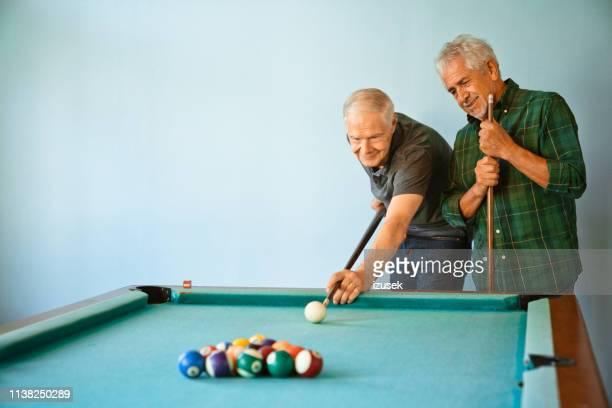 senior men playing pool ball at nursing home - old men playing pool stock pictures, royalty-free photos & images