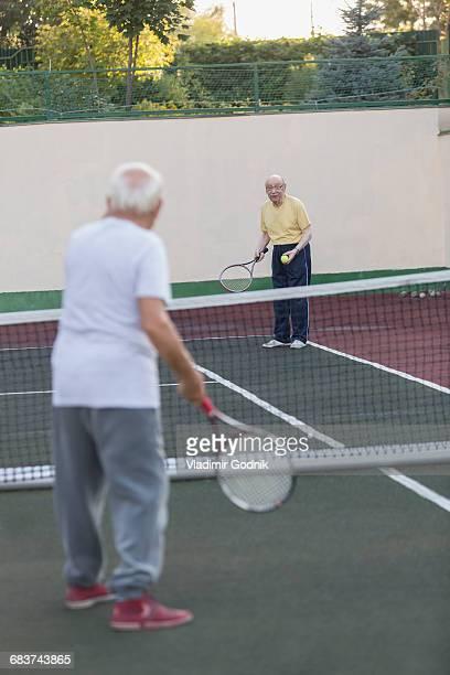 senior men playing tennis at court - trefferversuch stock-fotos und bilder