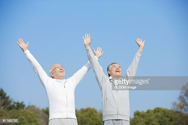 Senior men raising hands