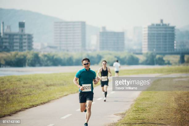 senior men running a marathon in the city - marathon stock pictures, royalty-free photos & images