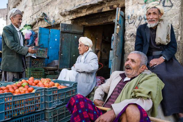 Senior men selling vegetables at street market