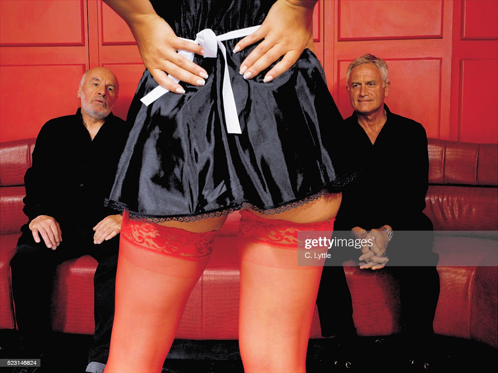 Senior Men Staring At Woman In French Maid Costume Stock Photo