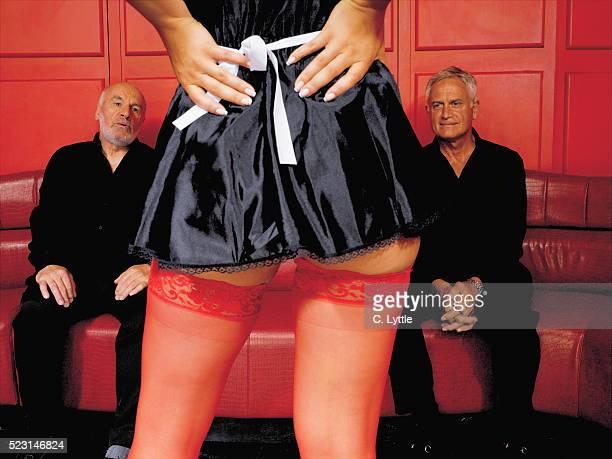 senior men staring at woman in french maid costume - lap dance stock-fotos und bilder