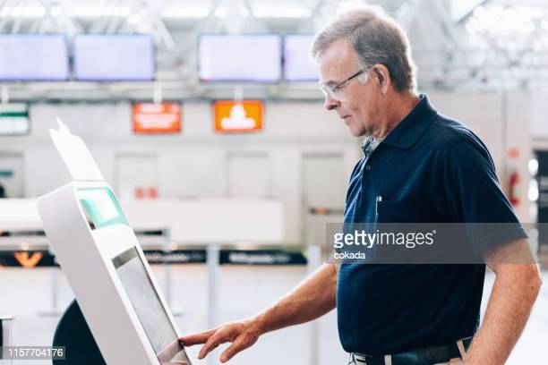 senior men using check in totem at the airport - totem pole stock pictures, royalty-free photos & images