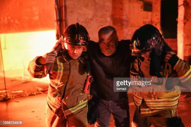 senior men victim of a fire being rescued by two firefighters - burns victims stock pictures, royalty-free photos & images