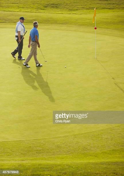 Senior men walking on golf course