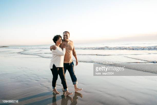 senior men walking with senior women on the beach - pacific ocean stock pictures, royalty-free photos & images