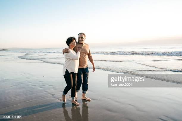 senior men walking with senior women on the beach - retirement stock pictures, royalty-free photos & images
