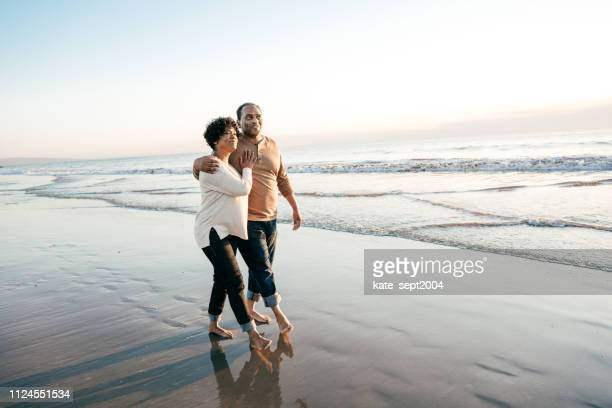 senior men walking with senior women on the beach - interracial wife stock pictures, royalty-free photos & images