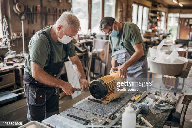 senior men with protective face masks rebuilding an engine in workshop - construction industry stock pictures, royalty-free photos & images