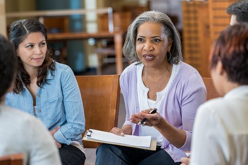 Senior mental health professional facilitates support group 962642012