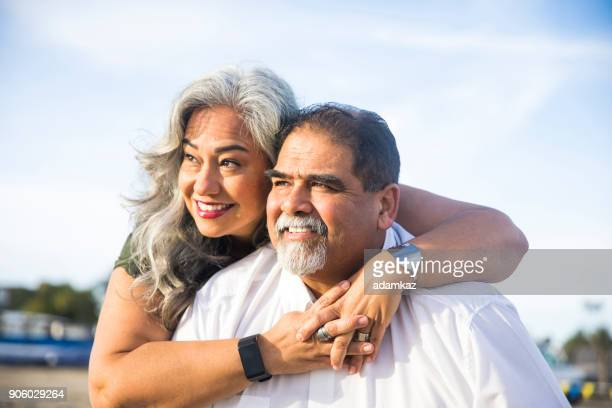 senior mexican couple piggyback at the beach - chubby men stock photos and pictures