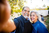 Senior Mexican Couple taking a selfie at BBQ