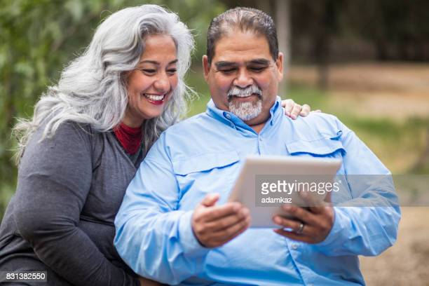 senior mexican couple using tablet - divergent film stock photos and pictures