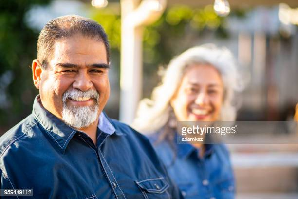senior mexican man smiling with wife in the background - mexican ethnicity stock pictures, royalty-free photos & images