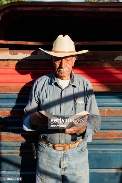 シニアのメキシコ人男性に立って、聖書を読む