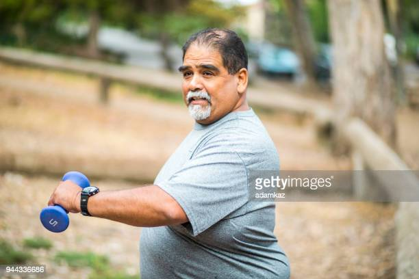 senior mexican man working out lifting weights - overweight stock pictures, royalty-free photos & images